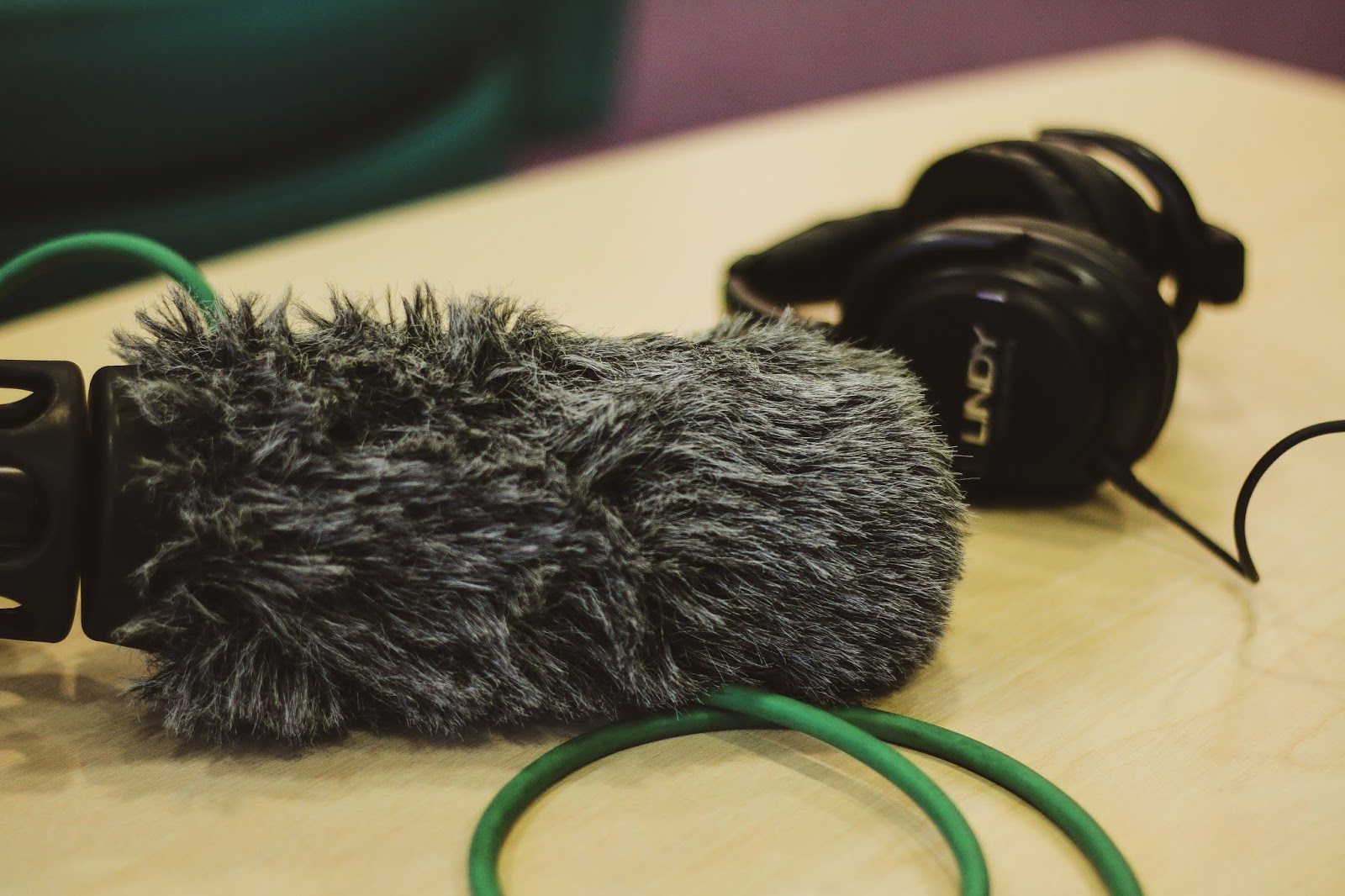 A close up photo of sound equipment on set of a film shoot. The photo shows a shotgun microphone on a pistol grip and headphone next to it.