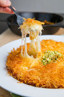 A pastry consisting of hot cheese in between layers crispy shredded phyllo dough in a sw Kanafeh/Künefe (Sweet Cheese Pastry) Recipe