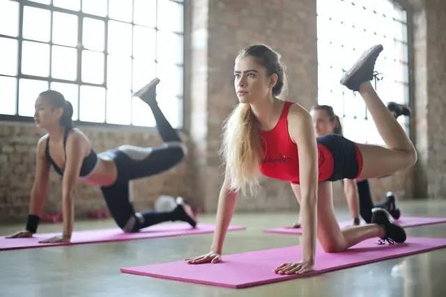 Dos mujeres haciendo ejercicio sobre el piso de un gimnasio