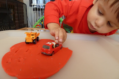 Child playing with a car in play dough