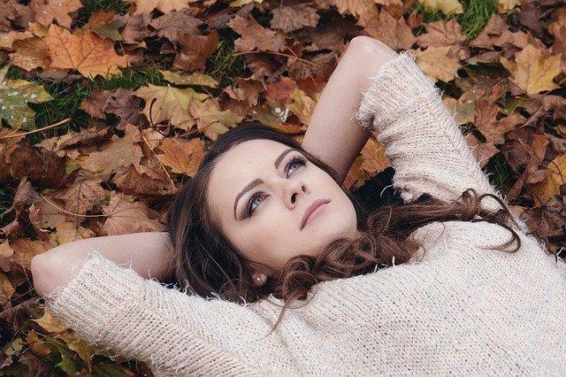 Mulher deitada sobre folhas, com olhar pensativo