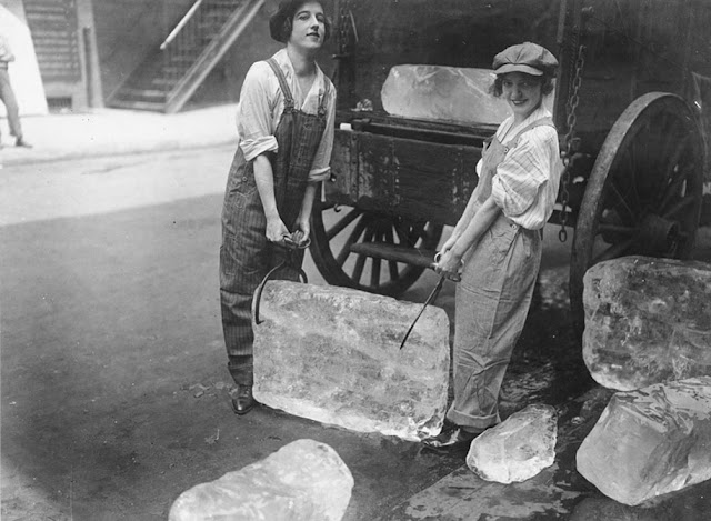 Two young women wearing overalls and caps, deliver a huge block of ice in 1920. Oh Wait and other stories of the Refrigerator. marchmatron.com