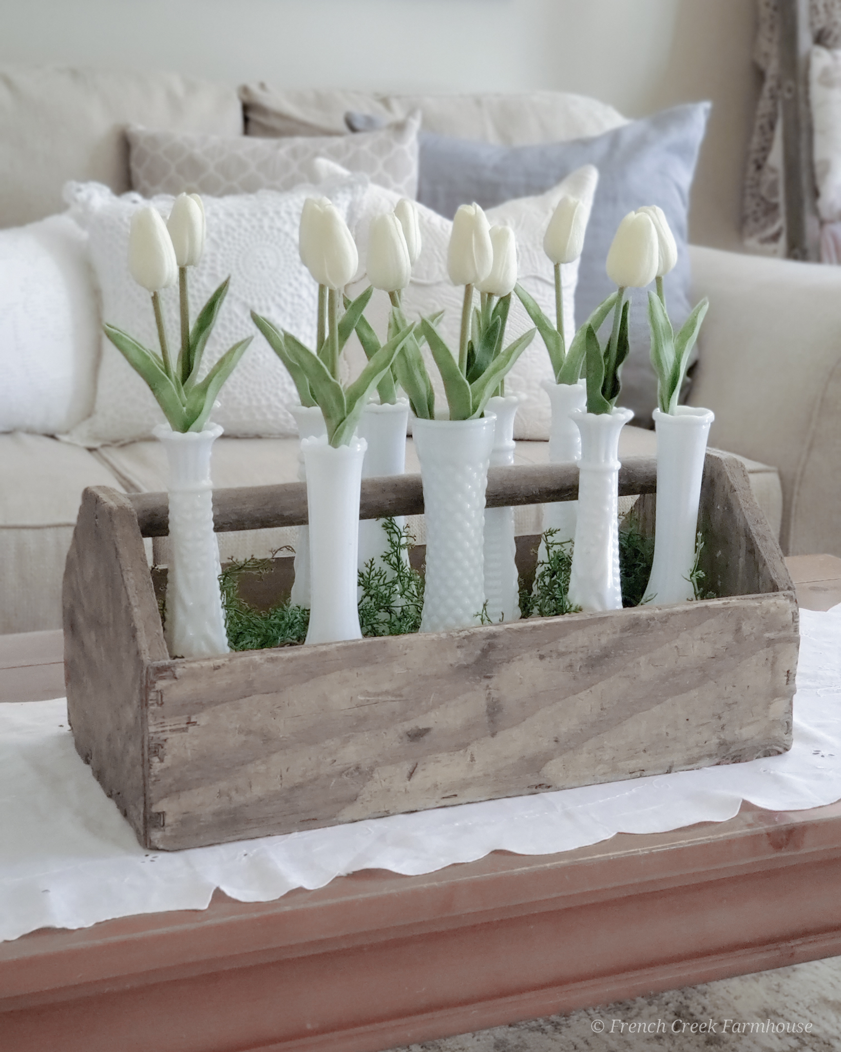 Modern farmhouse spring living room with white tulips and milk glass vases in wood toolbox
