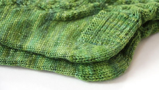 Detail of hand-knit green socks with darned heels on a white background.