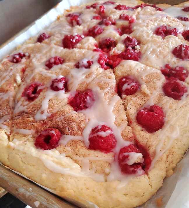 these are scones with red rasberries on top a cinnamon and sugar coating with a drizzle of icing on a sheet pan
