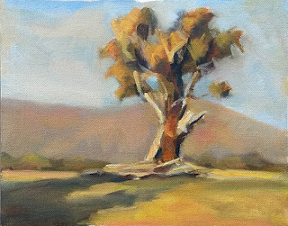 Oil painting of a eucalypt in front of a distant mountain range.