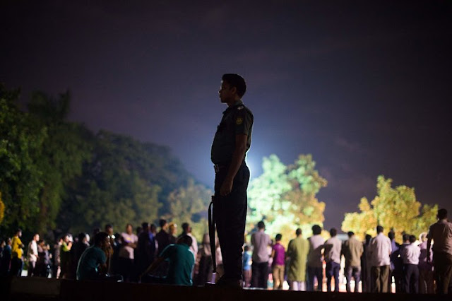 A Bangladeshi police officer overseeing a group of peace activists who sang and lit candles in a park on Sunday after a bloody siege at a restaurant in the capital, Dhaka. The attackers had declared allegiance to the Islamic State. Credit