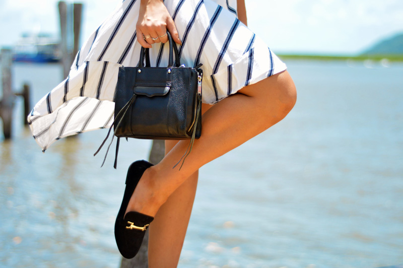 outfit details gucci style loafers rebecca minkoff micro bag and assymetric striped skirt in front of sea summer outfit