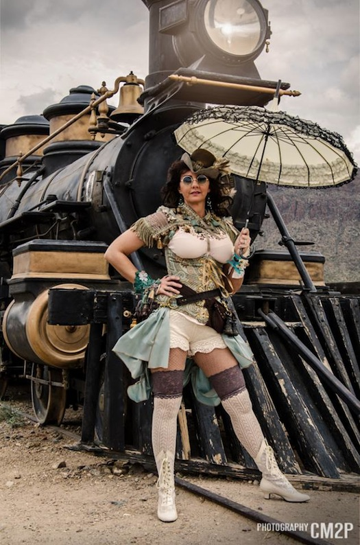 woman wearing sexy steampunk clothing in a cowgirl old west/western style in blue and white with a parasol, sunglasses, corset, bolero, bloomers and skirt
