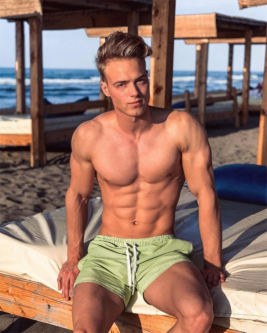 cute-blond-shirtless-male-model-sixpack-abs-green-shorts-beach-sunset