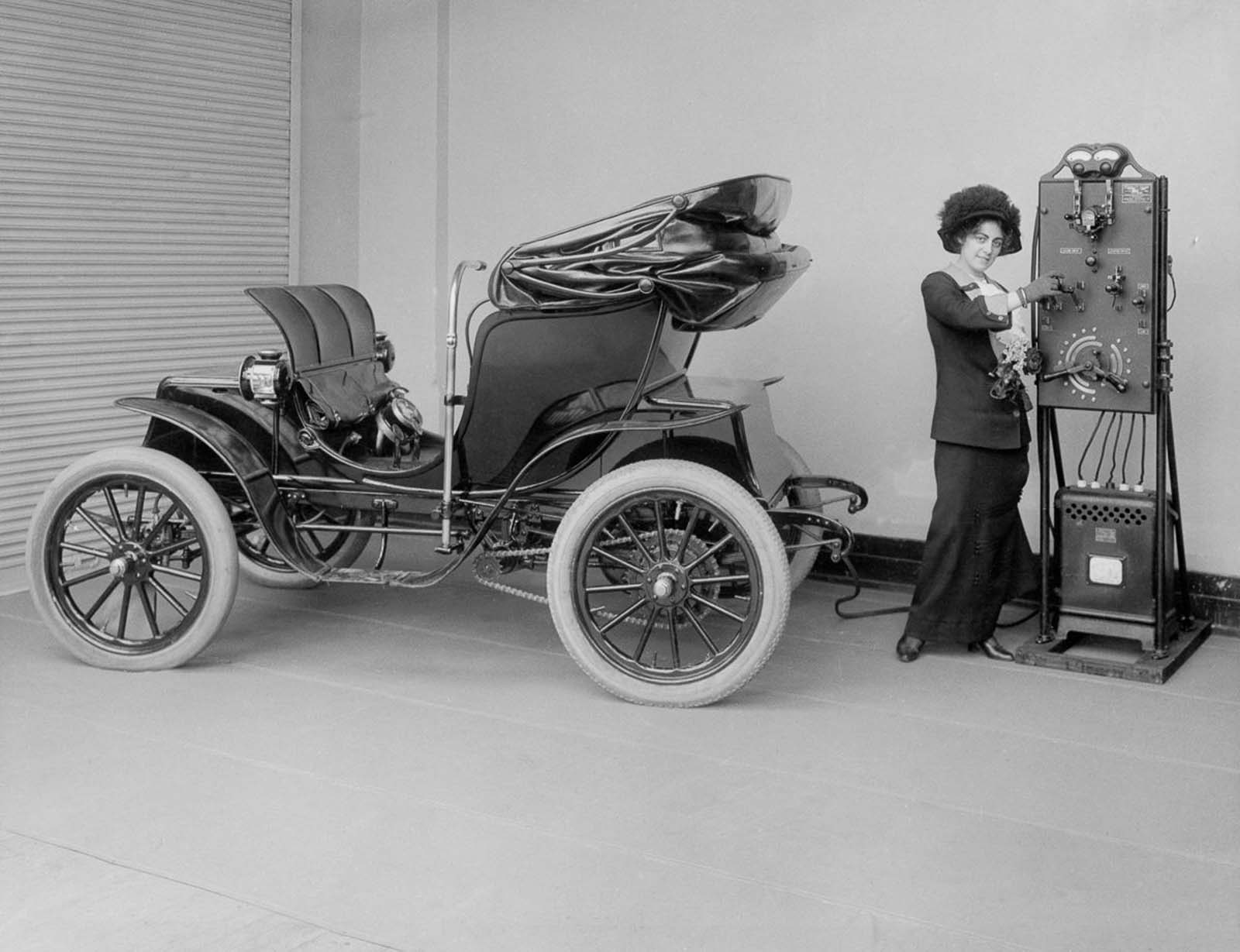 A woman uses a hand-cranked battery charger to charge her electric Columbia Mark 68 Victoria automobile. The Pope Manufacturing Company made the car in 1906 and the charger in 1912.