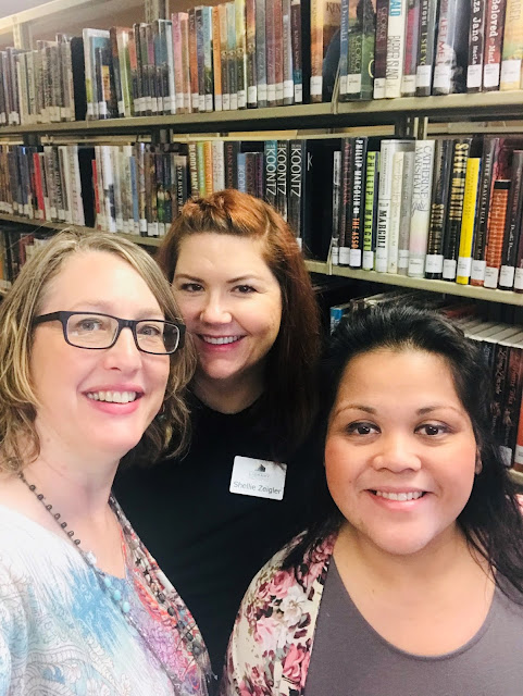 Three women, one wearing glasses, take a selfie in front of shelves of library books.