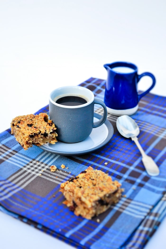 Black coffee served with Scottish Oaty Walnut and Raisin Flapjacks on a checked blue napkin