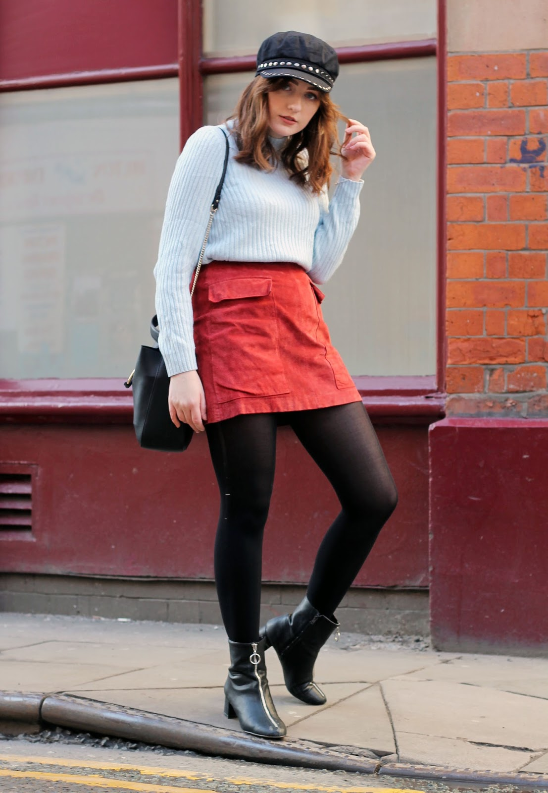 Liverpool style blogger with black studded topshop baker boy hat, baby blue turtle neck ribbed jumper, red suede a line skirt, black ring detail cross body bag and black zip up boots