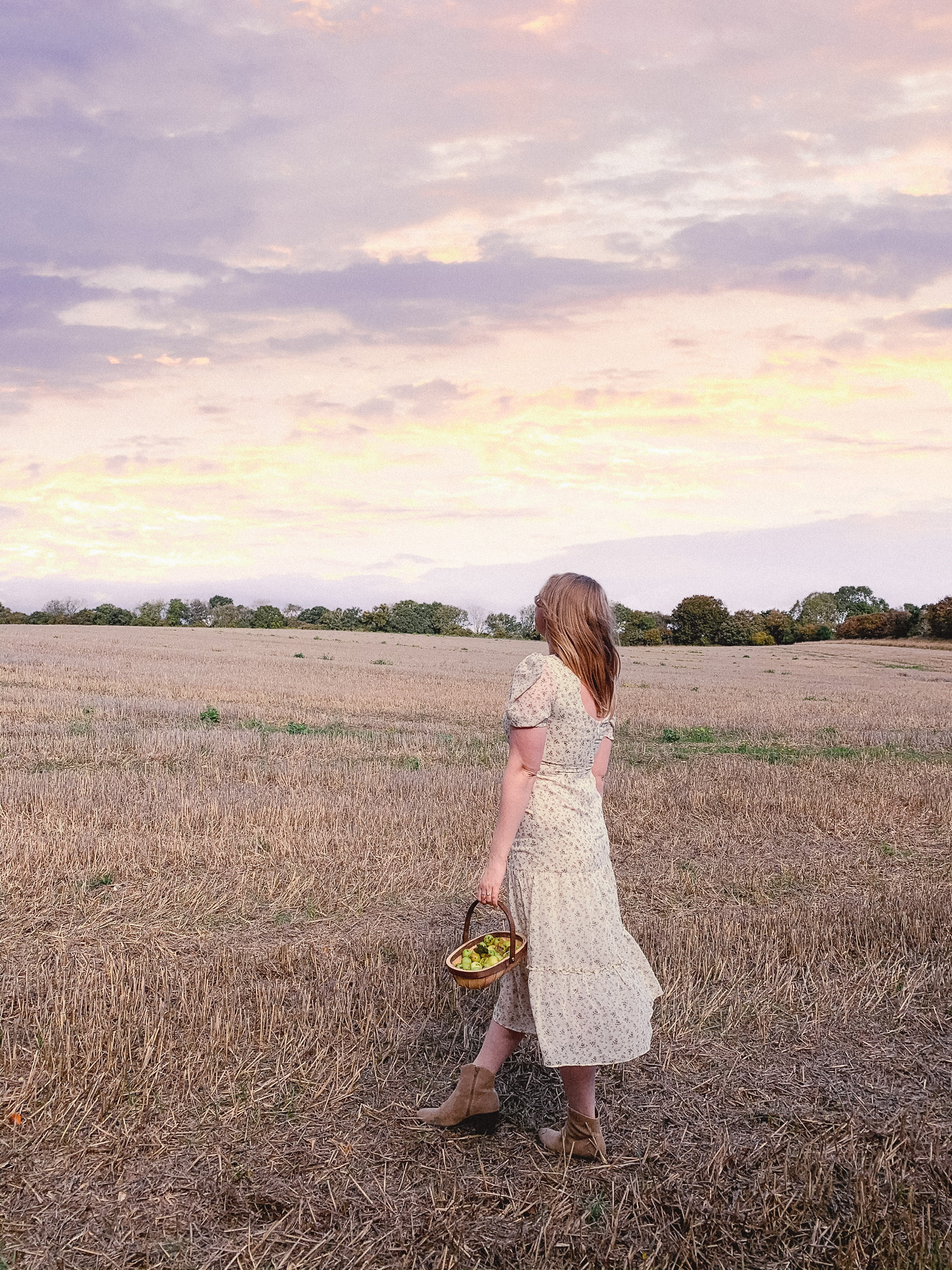 Fashion blogger standing in a Hampshire countryside field looking at the sunset