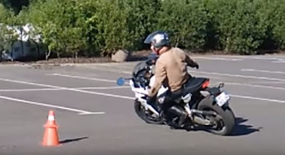 Motorcycle rider makes a turn with no hands on the handlebars.
