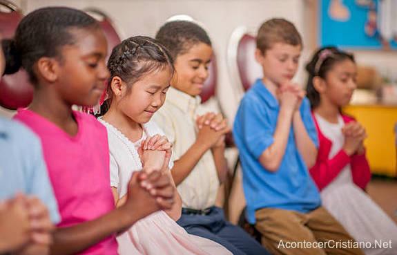 Niños orando antes de iniciar estudios bíblicos