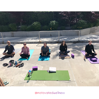Five people in easy pose sitting on yoga mats outside