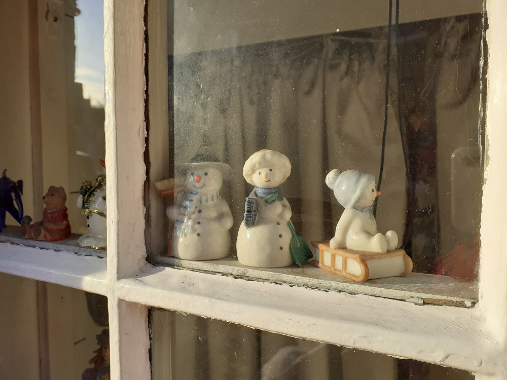 Snowpeople figurines on a window ledge