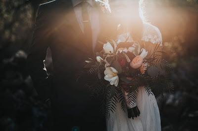 Novios en un jardín en zona y de sombra e iluminados por un rayo de sol