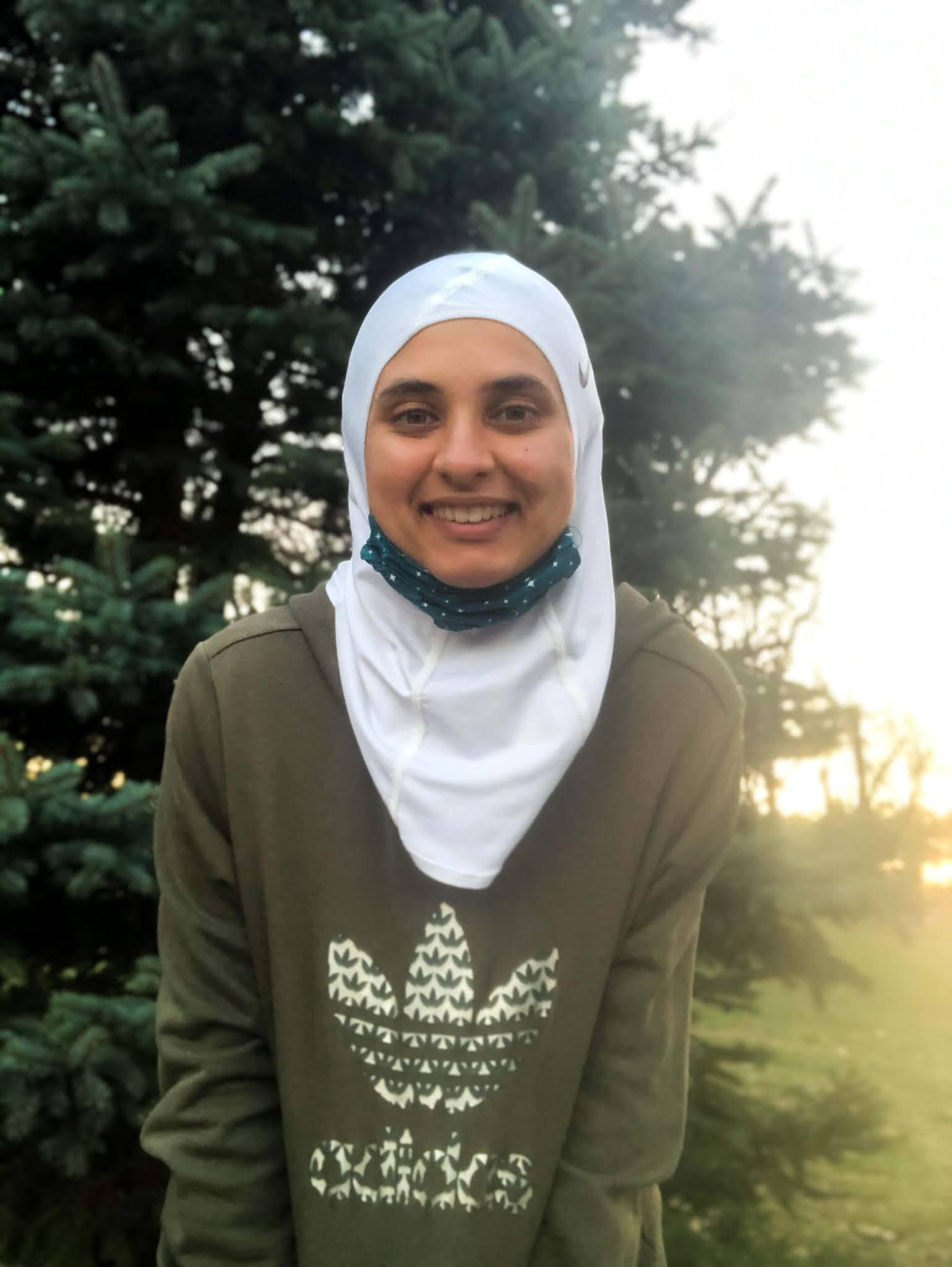 Sahara smiling in front of green tree - white nike hijab with blue starry mask pulled under her chin. Wearing green adidas sweatshirt