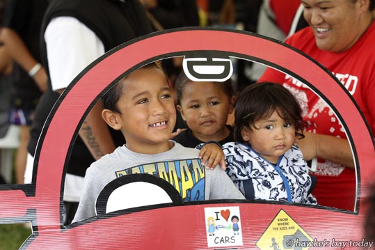 L-R: Iroam Mokaraka, 6, Henare Dunne, 2, Treyson Dunne, 1, all from Napier, getting their photograph taken behind the wheel of a cut-out car, at a stall run by Safekids Aotearoa, reinforcing safety messages for kids, in the Kai/Expo area - Waitangi Day The Big 9, Waitangi Day celebrations at Hawke's Bay Regional Sports Park, Hastings. photograph