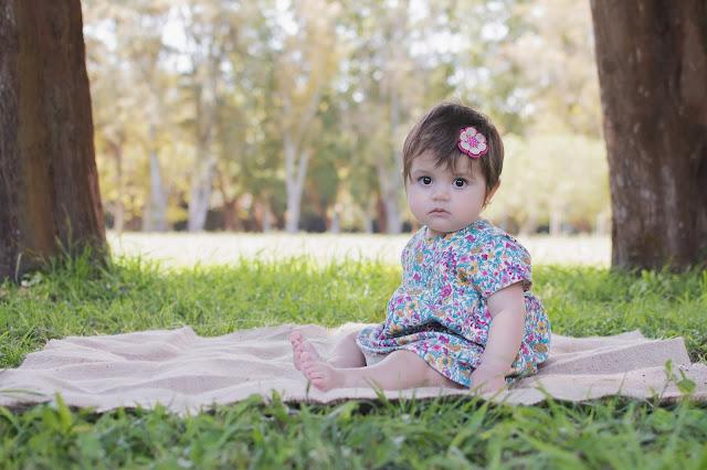 Fotografía de niña, en exteriores. Realizada por Leticia Martiñena, de Positive Fotógrafos, para el primer añito. En una bella locación al aire libre en la ciudad de Zaballa.