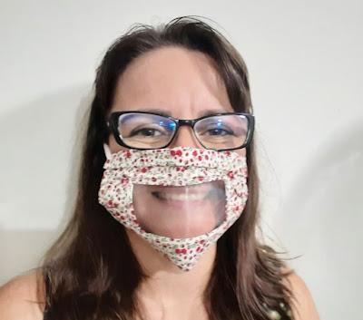 Pessoa usando um modelo feminino de máscara com uma parte de plástico transparente na altura da boca