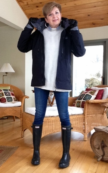 woman in black rubber boots, white sweater, Gortex jacket, and jeans