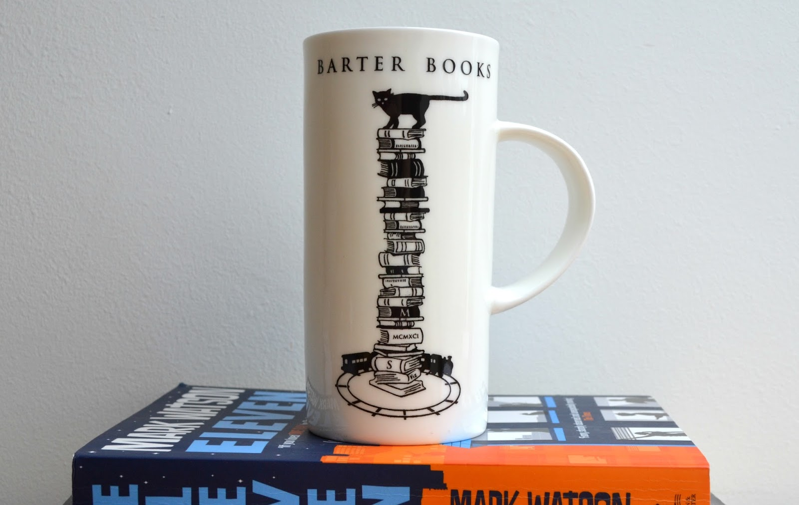 Barter Books mug with a stack of books, a cat and a train on it.