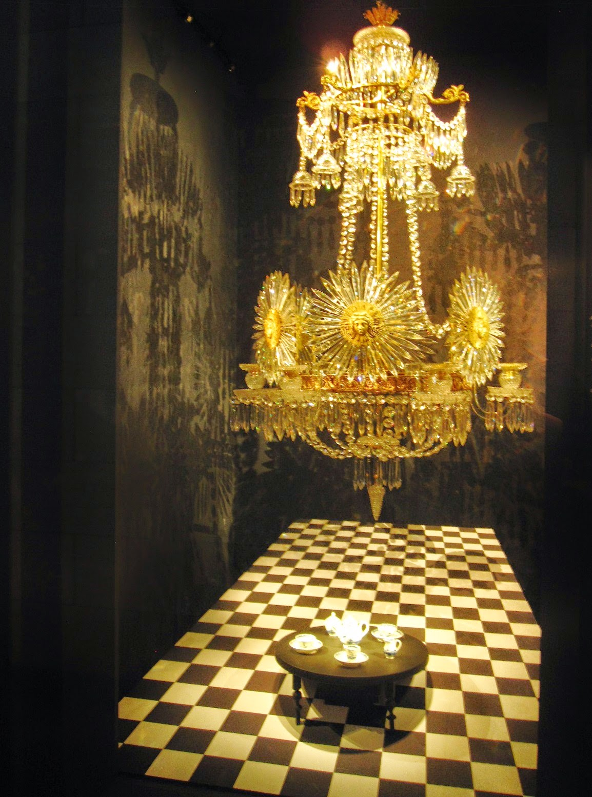 Miniature tea set on display in a museum, on a miniature antique table with a full-sized antique chandelier above.