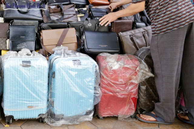 An attendant rearranges suitcases and bags yesterday at a shop in central Phnom Penh. Hong Menea