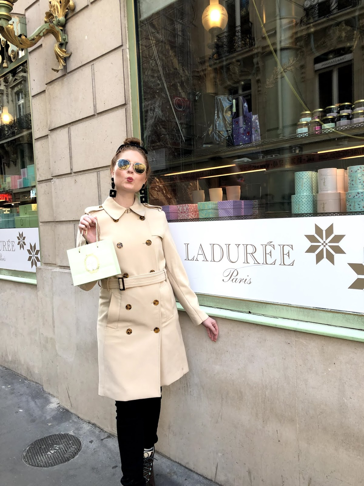 tampa blogger amanda burrows of affordable by amanda wears a tan trench coat while snacking on macaroons from laduree in paris, france.