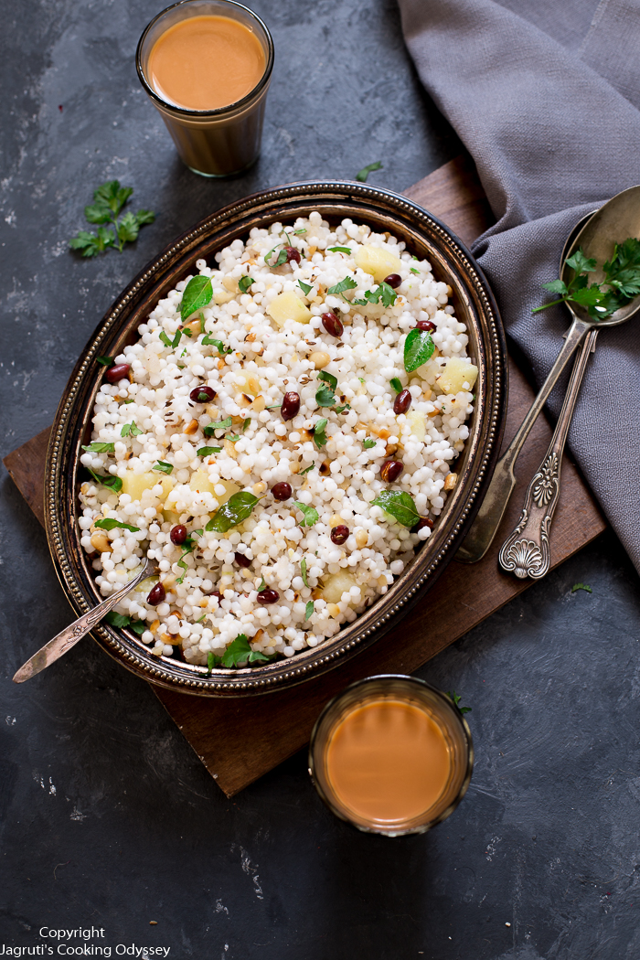 This sago pearl pulao or pilaf is served in a metal tray with a cup of chai tea