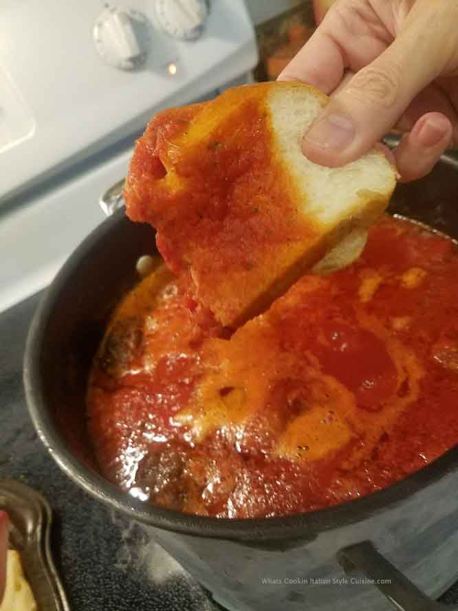this is a pot of sauce and Italian bread dipping into it for a taste