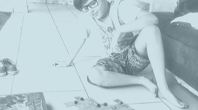 Foto de pai e filho brincando com jogo de tabuleiro.