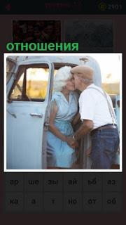 около машины стоит пожилая пара и целуются