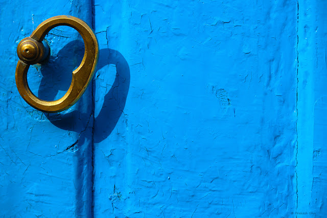 A Minimalist Photo of a Brass Know of a Textured Blue Indian Door
