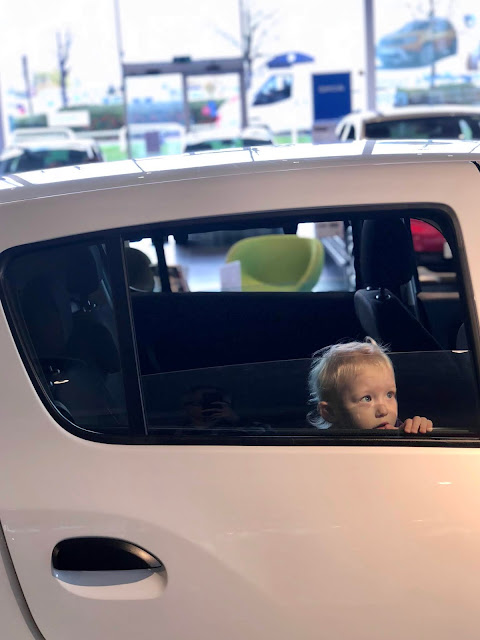 A toddler in the back seat of a car in a car show room