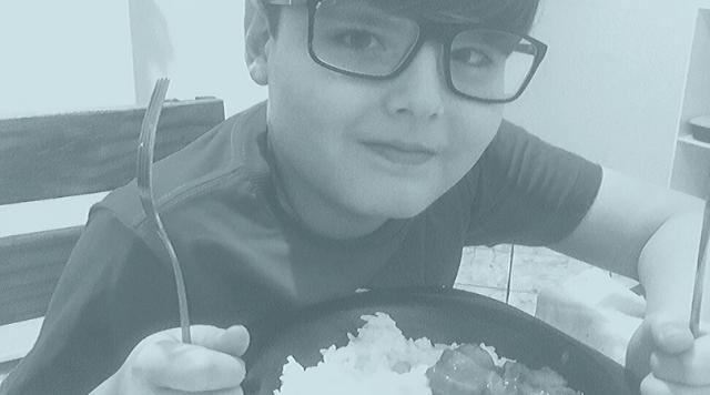 Foto do meu filho jantando a comida que preparei: arroz a grega, purê de batata e salsicha no molho.
