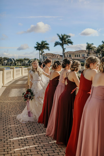 wedding party walking in country club setting with palm trees