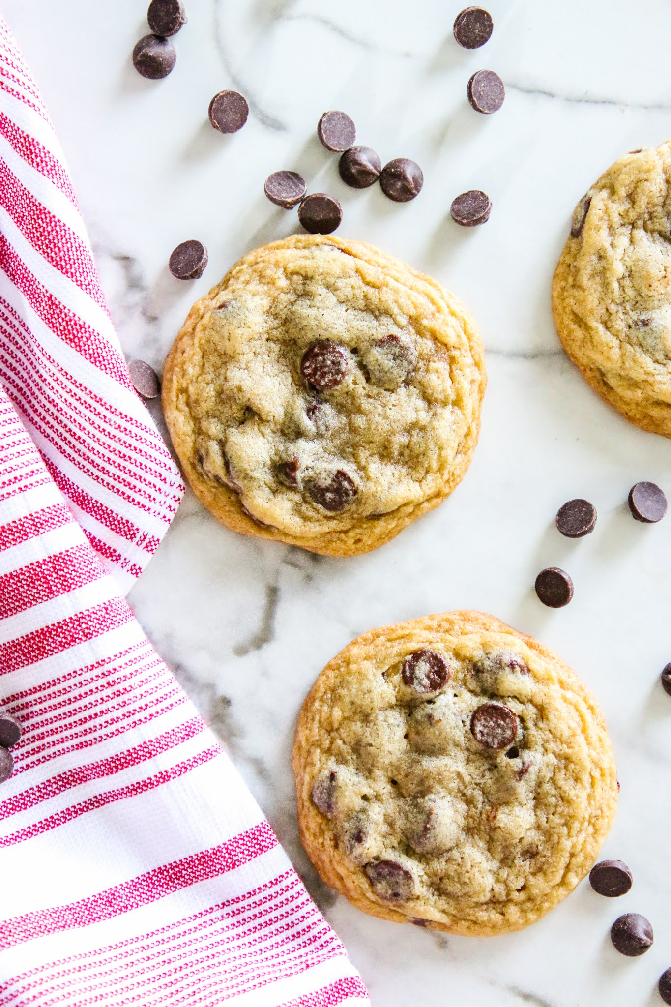 Three chocolate chip cookies on a marble table with scattered chocolate chips and a red towel
