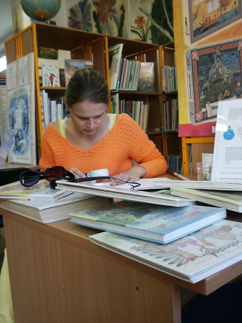 Linda v knihovně čte pomocí lupy