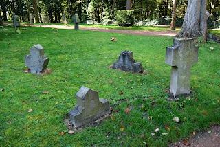 Vier alte Grabsteine stehen auf einer Wiese. Drei von ihnen sind bereits bis zur Hälfte in die Erde eingesunken.
