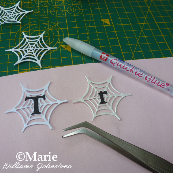 Adding letters to the middle of paper spider webs to spell a Halloween phrase