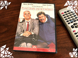 DVD of Planes, Trains, and Automobiles with Steve Martin and John Candy on the cover—sitting on dark wood table top with an old DVD remote beside it.