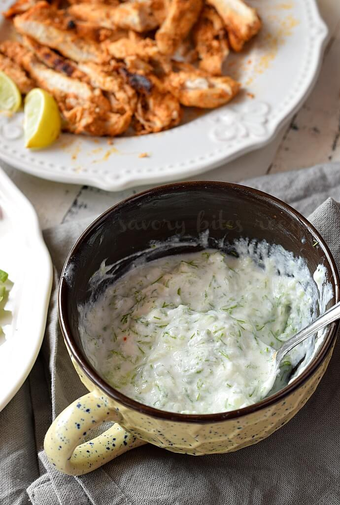 a white and black bowl with easy tzatziki sauce and a plate with shredded chicken