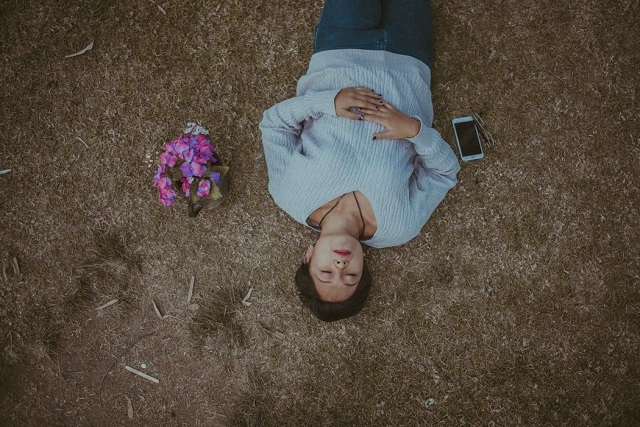 woman lying down on the ground with flowers and phone on side
