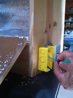 homem instalando caixa de luz na estufa de madeira