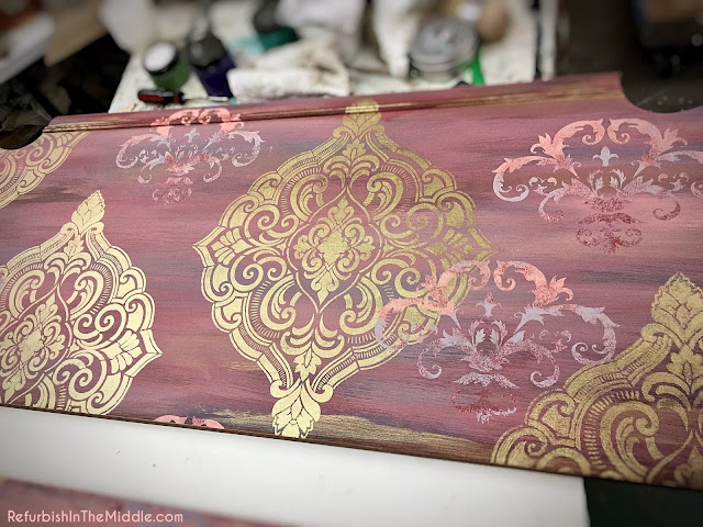 headboard of a bed in the final stage using chalk paint and a stencil, shades of pink